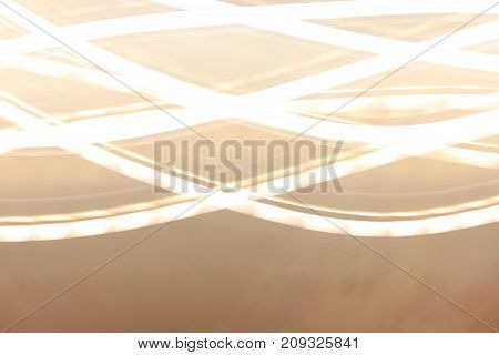 Abstract Wallpaper Background with Bright Light Lines Shine Pattern. Yellow white curved colorful glowing lights way effect. Soft blurred bokeh pathway with empty copy space at the bottom of image.