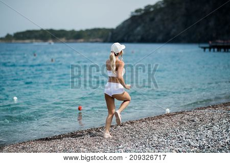 Back view of a blonde girl running against blue background.