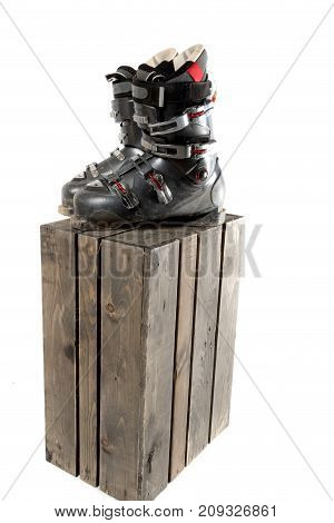 Ski boot sitting on a wooden crate isolated on a white background