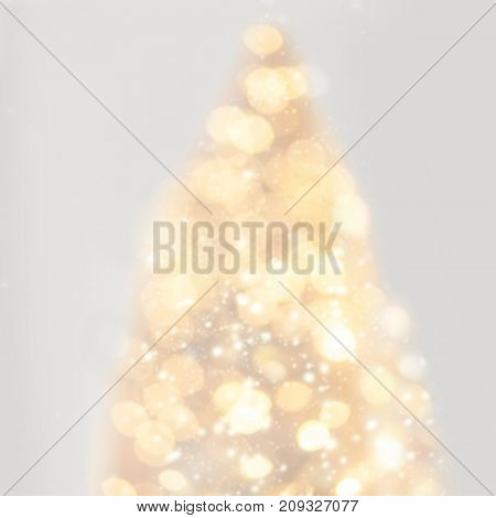 Abstract sparkling lights glittering in a shape of Christmas tree with yellow bokeh. Defocused Xmas tree concept idea poster card