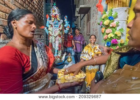 KOLKATA INDIA - JUNE 17 2017 - Female Hindu devotees worshipping Goddess Kali at night during Kali Puja Hindu festival of Deepavali or Diwali. Celebtated all over India. Shot under mixed light.