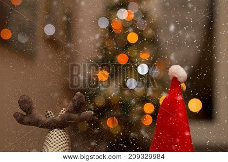 Rudolf and Santa Claus under the snow with lights in the background