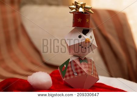 macro paper snowman on red carpet to december
