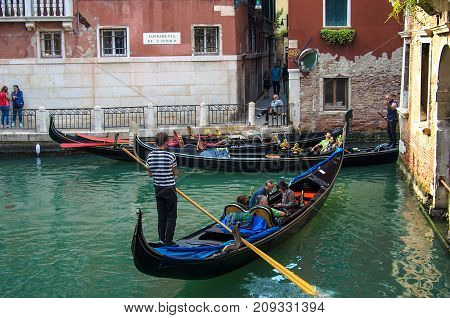VENICE ITALY - SEPTEMBER 29 2017: Canal in Venice with gondolas gondoliers and tourists old houses on Venice street Fondamenta de L'anzolo.
