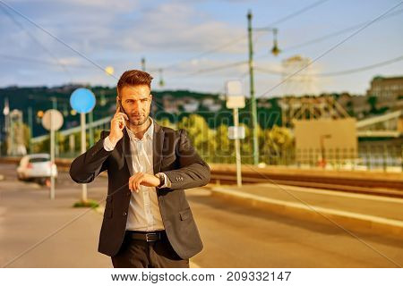 A handsome young businessman walking on the street on the riverside while talking on his phone and checking his watch