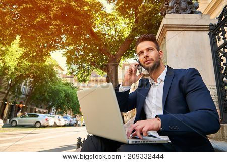A handsome young businessman sitting on the stairs on the street with his laptop while talking on a phone