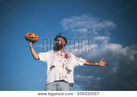 Halloween soldier zombie with red blood on cloudy blue sky. Man holding pumpkin on hand. War victim and horror concept. Hipster in bloody torn tshirt with jack o lantern. Autumn holiday celebration.