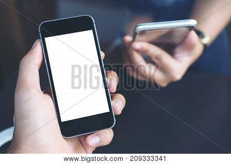 Mockup image of businessman's hand holding black mobile phone with blank white screen with businesswoman holding another mobile phone in background
