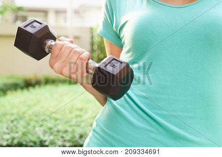 Hand of fat woman holding dumbbell for exercising in public park