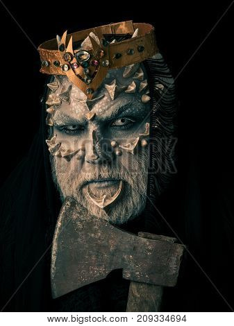 Man with axe on black background. Monster face with white eyes thorns and warts. Demon with crown on head. King or evil creature with dragon skin and beard. Horror and death concept.