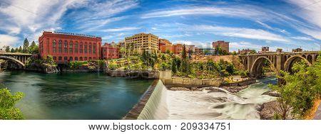 SPOKANE, WASHINGTON, USA - JULY 4, 2017 : Panoramic cityscape view of Washington Water Power building and the Monroe Street Bridge along the Spokane river, in Spokane, Washington.