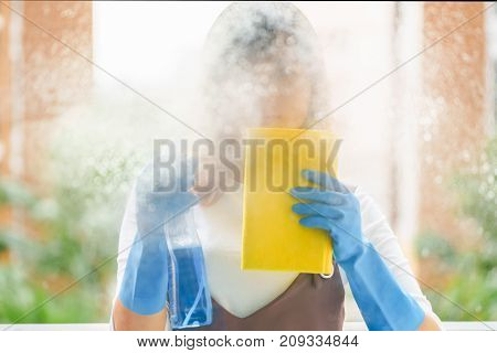 Woman housekeeper cleaning the mirror with yellow cloth