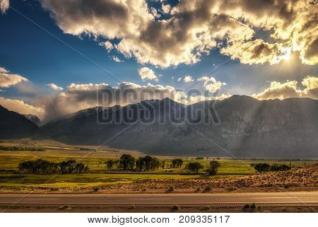 Play of lights and clouds before sunset above Sierra Nevada from route 395 in California, USA