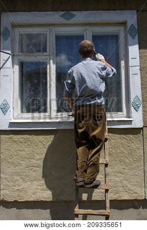 the pensioner stands on the windows of the house and cleans the paint on the window