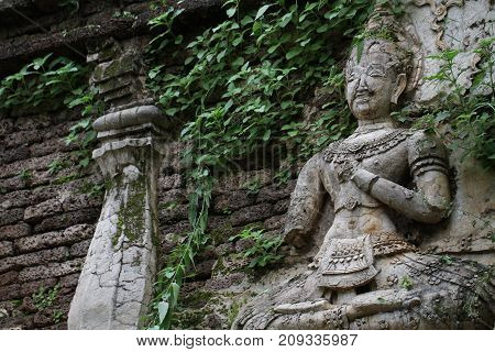 400 years old ruined ancient standing and praying of male angel statue at Chiangmai, Thailand, buddha statue without some of body part, historical decorated wall temple covered with green leaf