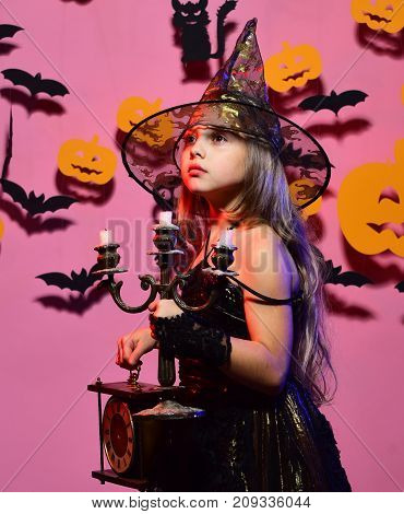 Kid in spooky witches costume holds old clock and chandelier. Little witch wearing black hat. Halloween party and decorations concept. Girl with interested face on pink background with spooky decor