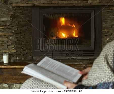 Man Reading A Book, Sitting In A Rocking Chair With Knit Plaid In Front Of A Fireplace