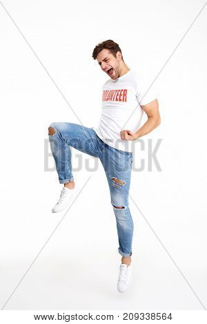 Full length portrait of a happy amused man in volunteer t-shirt celebrating isolated over white background