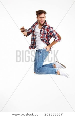 Full length portrait of an attractive cheerful man taking a selfie while jumping and posing isolated over white background