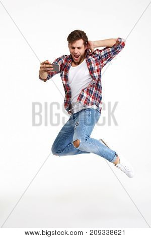 Full length portrait of a young attractive man taking a selfie while jumping and posing isolated over white background