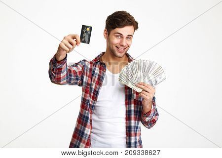 Portrait of a happy smiling man holding bunch of money banknotes and showing credit card isolated over white background