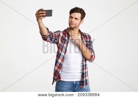 Portrait of an attractive young man taking a selfie while standing and pointing finger isolated over white background