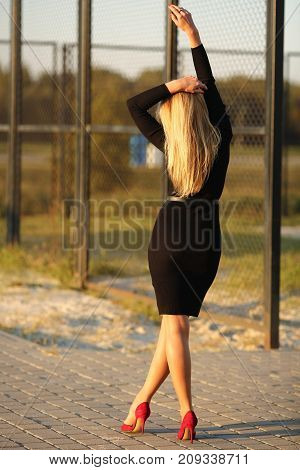 Young slender woman in a black dress