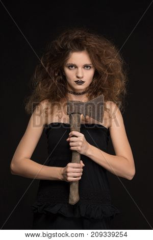 Beautiful girl with a gothic make-up as a witch smiles and holds an ax on a black background for the holiday of Halloween