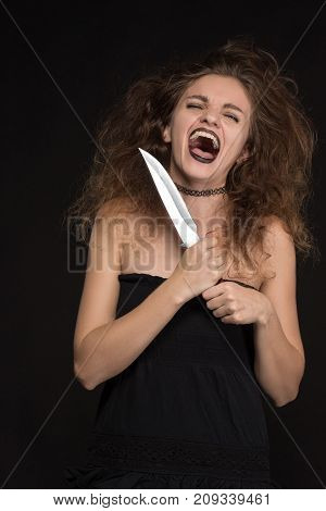 Beautiful girl with gothic makeup as a witch smiles and holds a knife on a black background for the holiday of Halloween