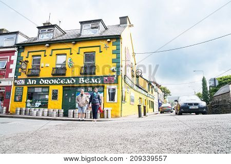 DINGLE IRELAND - AUGUST 12 2017; Couple wait to cross street outside small Irish pub on village street corner bright yellow and green with beer barrels on footpath outside.