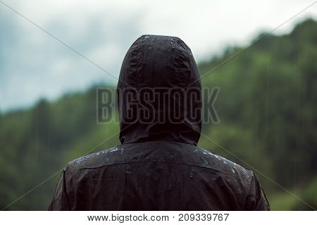 Rear view of hooded man standing in rain on cold cloudy autumn day getting drenched