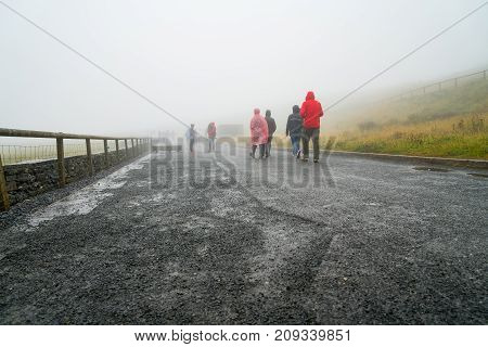 CLIFFS OF MOHR IRELAND - AUGUST 11 2017; Group of people dressed in wet weather clothing walk away through mist on path leading to Cliffs of Mohr