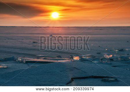 Field of ice hummocks on the frozen Lake Baikal. Sunset. Russia