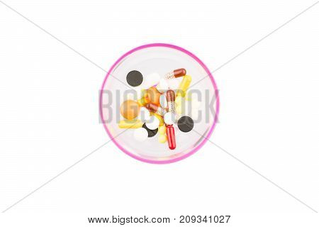 Pills on isolated white background in a cup