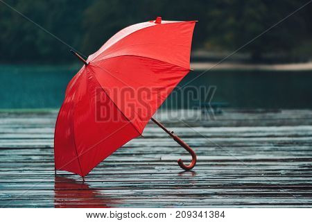 Red umbrella on rain personal accessory forgotten on old wooden pier