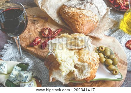 A glass of dry red wine and Italian Focaccia bread with cheese and a cheese platter with figs and Gorgonzola brie DorBlu and grapes. Selective focus. The horizontal frame.