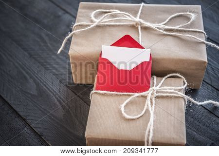 Gifts wrapped in brown vintage paper tied with white flax string and a red envelope on them with blank paper displayed on an old black wooden table.