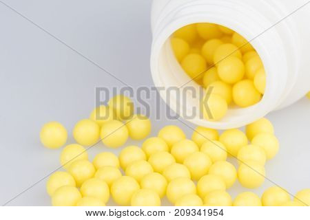 Container with scattered yellow pills closeup on the grey medical table