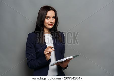 Technology. Business woman with digital device. Beautiful office worker at gray studio background with tablet