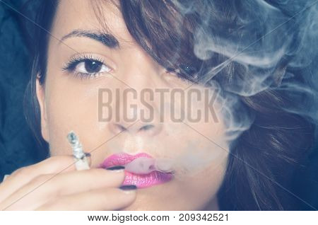 Close up portrait of beautiful young girl smoking cigarette with a lot of cigarette smoke