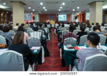 Abstract blurred photo of conference hall or seminar room which have Speakers on the stage with attendee background Business meeting concept