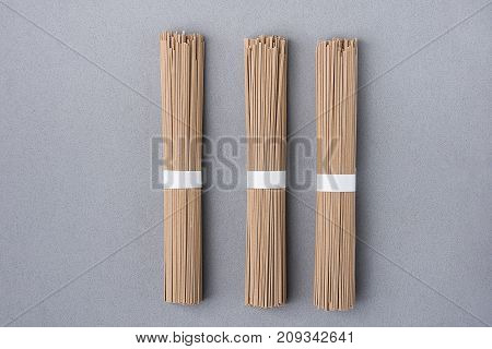 Bundles of Thin Soba Noodles Tied with White Paper Ribbon on Grey Background. Japanese Cuisine New Years Eve Dish. Clean Minimalist Style. Flat Lay. Copy Space