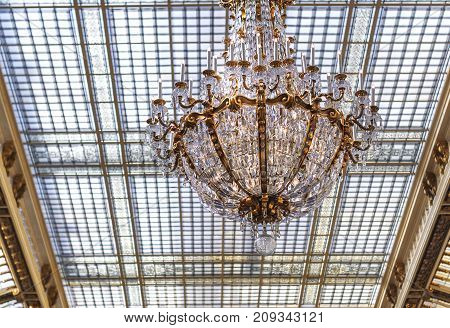 elegant crystal chandelier hanging from a glass ceiling