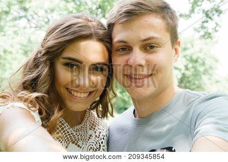 Couple of young girl and guy making selfie and smiling.