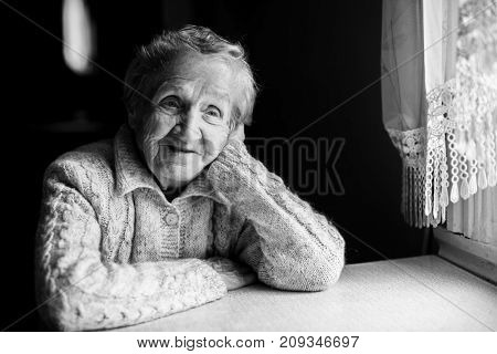 Portrait of an elderly woman sitting near the window. Black-and-white picture.