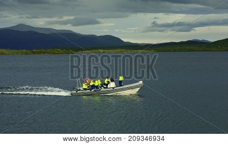 ABISKO, SWEDEN ON AUGUST 31. View of a rib boat comes in to the bridge on August 31, 2009 in Abisko, Sweden. Unidentified people, lake Tornetrask. Editorial use.