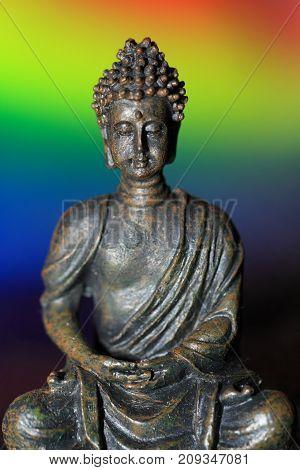 Meditative saint Buddha image against colorful background