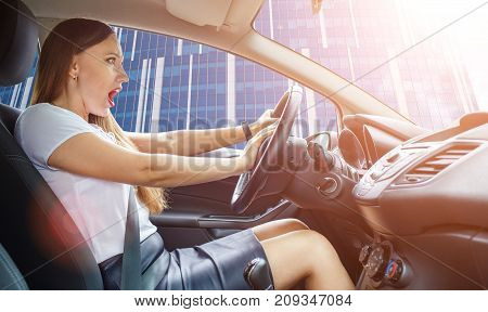 Young frightened driver woman squealing brakes in traffic jam