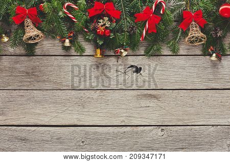 Xmas decoration, garland frame concept background, top view with copy space on gray rustic wooden surface. Christmas ornaments border with fir tree branches, bows, lollipop and bells
