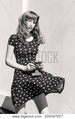 Young hipster woman with long hair in dress holding old film camera standing on windy place